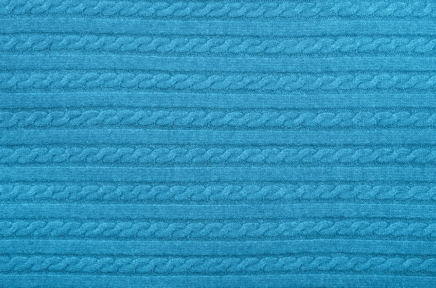 Close up background texture of pastel blue cable knitted wool jersey fabric sweater with row braid pattern