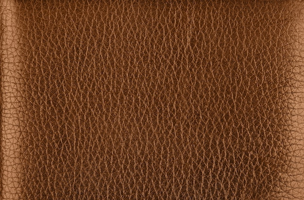 Close up background texture pattern of dark brown natural leather grain, directly above