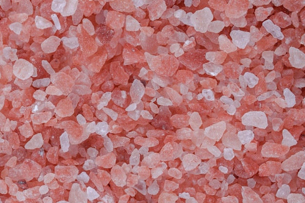Close up background texture of small fine ground crystals pink himalayan salt, elevated top view, directly above.