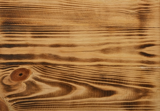 Close up background texture of vintage weathered burnt and brushed pine wood surface with knots and stains