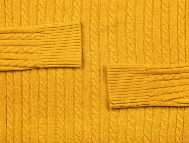 Close up background texture of warm yellow cable knitted wool jersey fabric sweater with row braid pattern