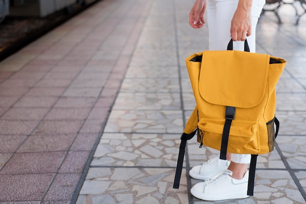 駅のクローズアップバックパックと女の子の足