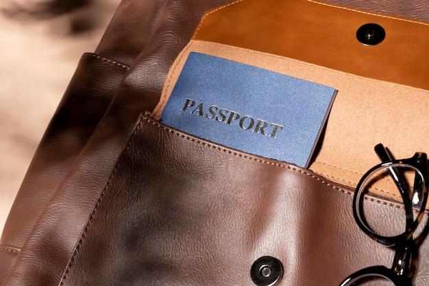 Close up zaino con passaporto e occhiali