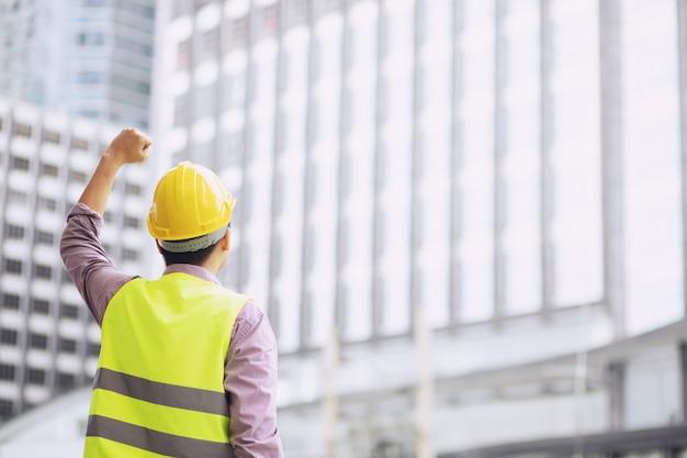 安全黄色のヘルメットを保持し、作業操作の安全のために反射服を着用するエンジニアリング男性建設労働者スタンドの背面図を閉じます。