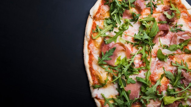 Close-up of bacon and arugula pizza over black surface