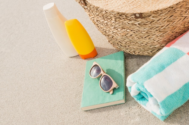 Close-up of bag and beach accessories on sand