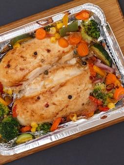 Крупным планом запеченные куриные грудки или филе с овощами и зеленью в металлическом контейнере на деревянной разделочной доске. вид сверху.
