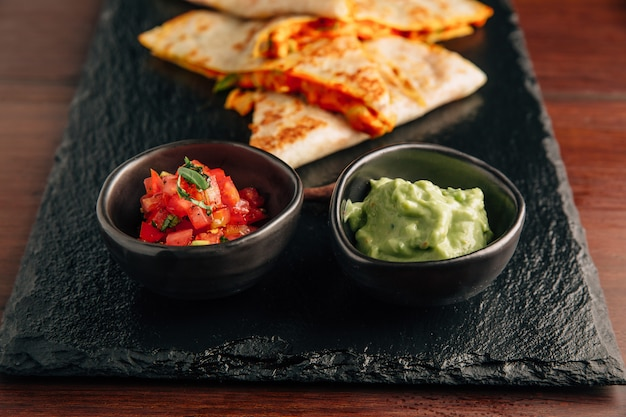 Close up baked chicken and cheese quesadillas served with salsa and guacamole.