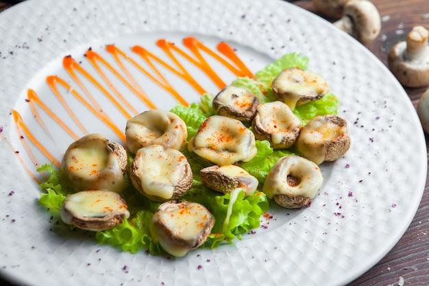 Закрыть запеченные грибы с сыром и листьями салата на белой тарелке