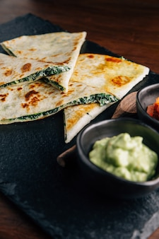 Close up baked spinach and cheese quesadillas served with salsa and guacamole.