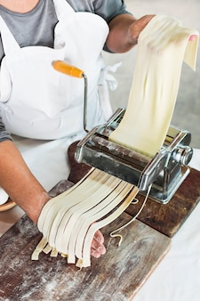 Close-up of baker cutting raw dough into tagliatelle on pasta machine