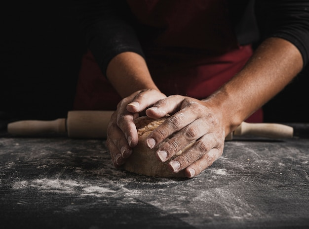Close-up baker hands kneading dough