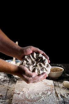 Close-up of baker kneading the dough over the table