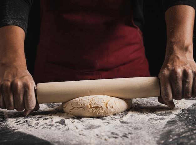 Close-up baker rolling dough composition