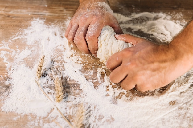 Close-up of baker's hand kneading dough on wooden table