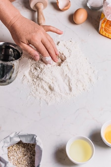 Close-up of a baker's hand with various baking ingredients on kitchen counter