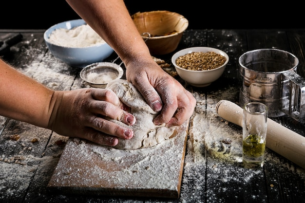 Close-up of baker's kneading the dough on chopping board with ingredients