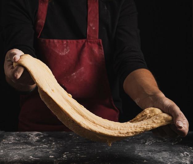 Крупным планом пекарь показывает состав теста