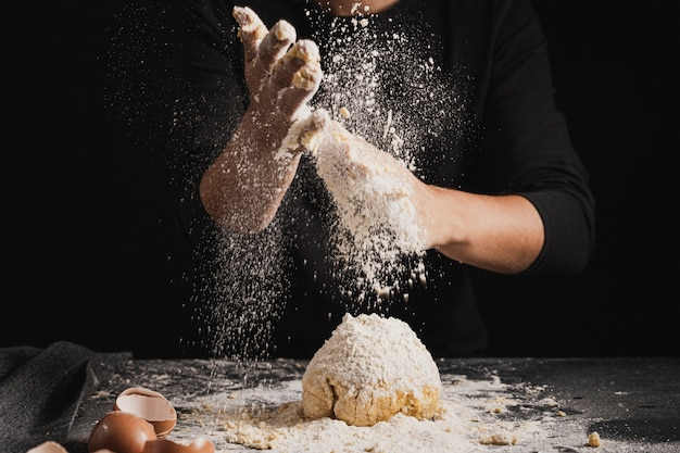 Close-up baker spreading flour on dough