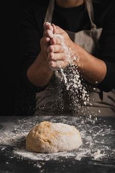 生地の上に小麦粉を広げるクローズアップのパン屋