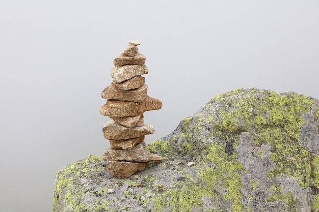 균형 잡힌 케른 또는 트롤 돌로 덮인 피라미드, 관광 메모리 표시, 하이킹 경로 표시를 닫습니다.