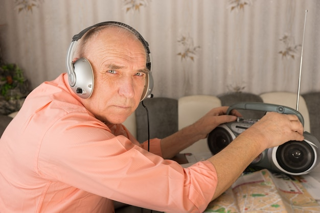 카메라를 보면서 헤드셋으로 카세트 플레이어에서 음악을 듣는 대머리 노인을 닫습니다.