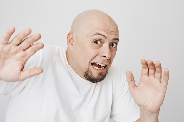 Close-up of bald scared bearded man screaming
