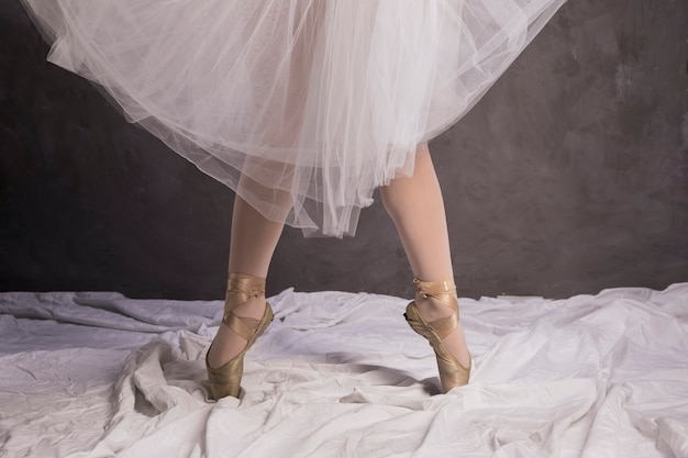 Close up ballerina in ballet shoes and skirt