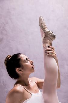 Close up ballerina holding her leg  up