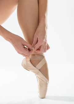 Close-up of ballerina puts on pointe shoes