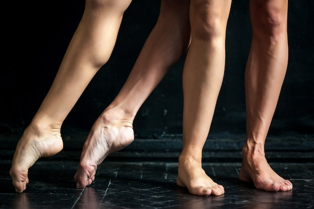 Close-up ballerina's legs on black wooden floor