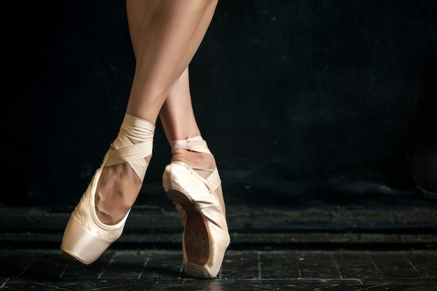 Close-up ballerina's legs in pointes on black wooden floor