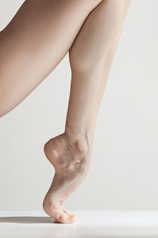 Close-up ballerina's legs on the white floor
