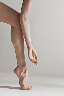 Close-up ballerina's legs on the white floor