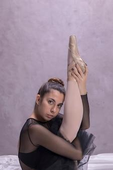 Close up ballerina stretching her leg up