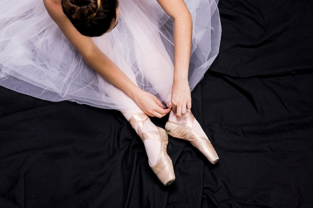 Close up ballerina tying her pointe shoes