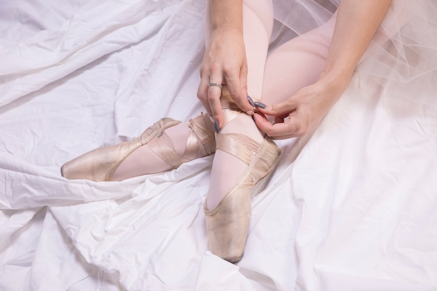 Close up ballerina tying pointe shoes