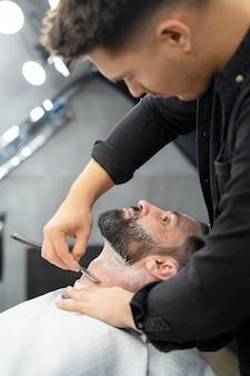 Close up barber grooming man