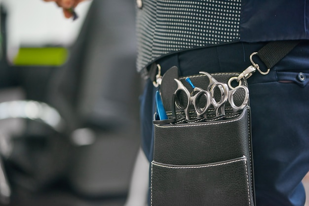 Close up of barber's leather bag with metallic sharp scissors hanging on waist.