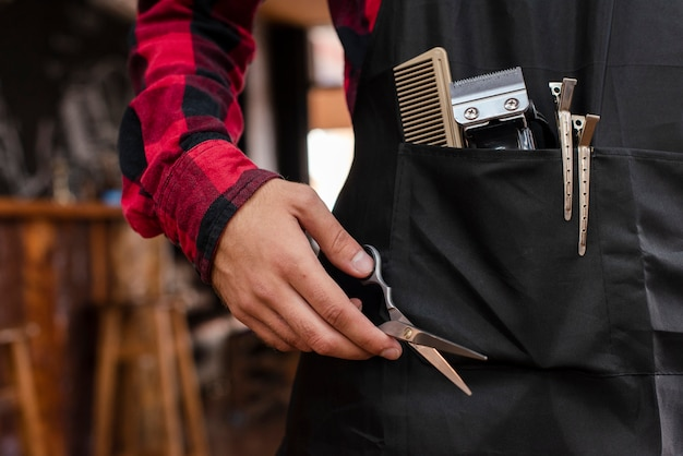 Close-up of barber tools in black apron