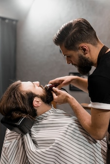 Close-up of a barber trimming man's beard with electric trimmer