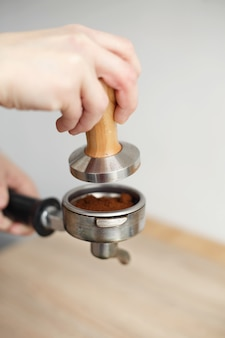 Close-up barista hand tamps ground coffee with tamper a into the holder for the coffee machine