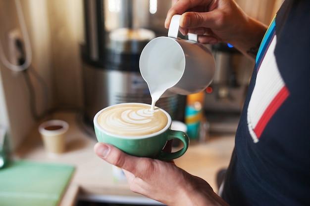 カフェラテアートを作るためにコーヒーカップに暖かい牛乳を注ぐバリスタの手を閉じます。コーヒーショップでプロのコーヒーカフェラテアート。