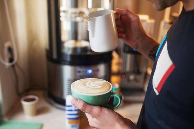 カフェラテアートを作るためのコーヒーカップに暖かい牛乳を注ぐバリスタの手を閉じます。コーヒーショップでプロのコーヒーカフェラテアート。