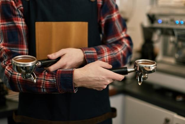 클로즈업, 앞치마를 입은 바리스타가 카페에서 커피를 갈고 있다