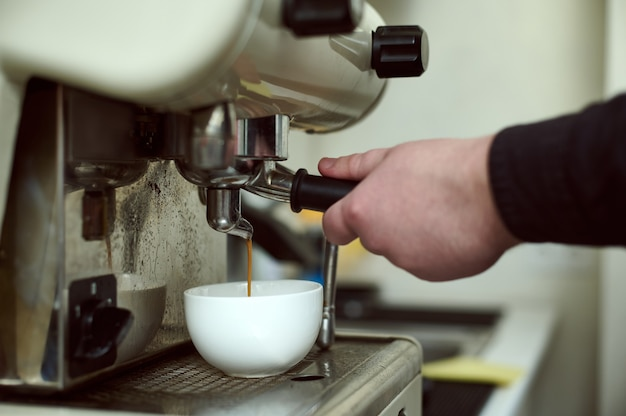 Close-up of barista's hands preparing espresso in the professional coffee machine
