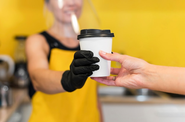 Close-up barista serving with face protection