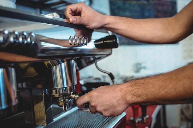 Close-up of barista using espresso machine at coffee house