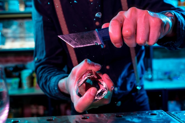 Close up of barman crushing a big piece of ice on the bar counter with a special bar equipment on it for a cocktail
