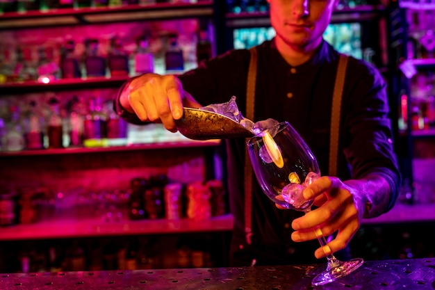 Close up of barman finishes preparation of alcoholic cocktail, pouring drink in neon light